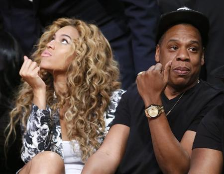 Singer Beyonce and her husband Jay-Z sit courtside before the NBA All-Star basketball game in Houston, Texas, February 17, 2013. REUTERS/Lucy Nicholson/Files
