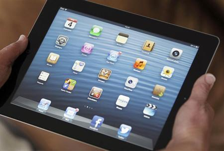 An illustration picture shows application icons on an Apple Ipad tablet held by a woman in Bordeaux, Southwestern France, February 4, 2013. REUTERS/Regis Duvignau
