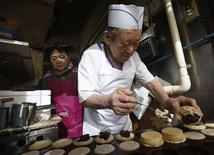 "Seventy-six-year-old Minekatsu Kinugasa (R) and his seventy-four-year old wife Kiyoko make ""imagawayaki' buns with sweet fillings at their shop in central Tokyo's Azabu-juban district, February 8, 2013. REUTERS/Issei Kato"