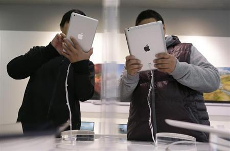 A sales assistant (L) holds an iPad mini next to a customer holding an iPad during the China launch of the iPad mini, in Wuhan, Hubei province, December 7, 2012. REUTERS/Stringer/Files