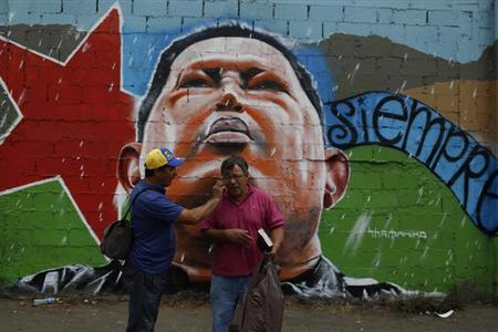A man talks on a mobile phone with the help of a friend as they stand in front of a mural showing Venezuela's late President Hugo Chavez near the military academy in Caracas March 12, 2013. REUTERS/Tomas Bravo