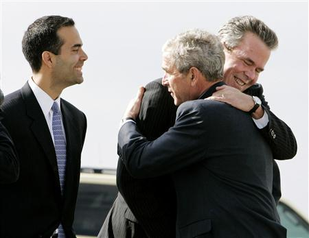 U.S. President George W. Bush (C) hugs his brother, former Florida Gov. Jeb Bush (R), while Jeb's son George P. Bush (L) smiles after arriving in Palm Beach, Florida March 18, 2008. REUTERS/Larry Downing