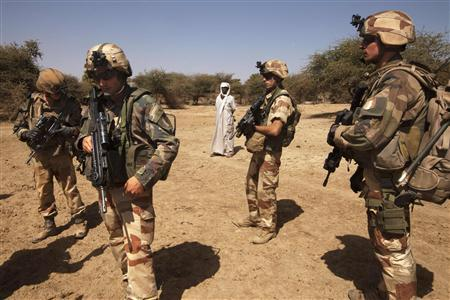 French soldiers stand guard next to a local resident outside Gao, Mali, March 9 2013. Picture taken March 9, 2013. REUTERS/Emmanuel Braun