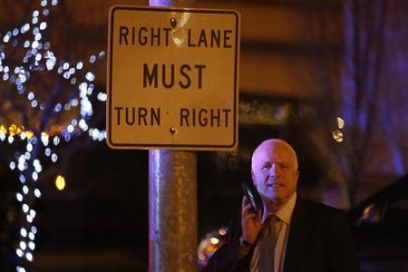U.S. Senator John McCain (R-AZ) talks on his phone as he and other Republican senators depart after a private dinner with U.S. President Barack Obama at a hotel near the White House in Washington, March 6, 2013. REUTERS/Jonathan Ernst