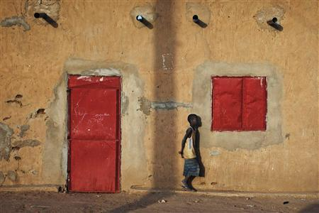 A boy walks past metal doors and windows on a house in Gao in this February 26, 2013 file photo. REUTERS/Joe Penney/Files
