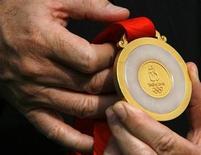 Президент BHP Billiton China Клинтон Дайнс демонстрирует золотую олимпийскую медаль перед официальной передачей на церемонии в Пекине 3 июля 2008 года. Правительство США открыло расследование в отношении горнорудной компании BHP Billiton Ltd, подозревая ее в коррупционных действиях. REUTERS/David Gray