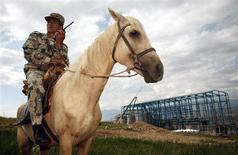 Сотрудник службы безопасности патрулирует территорию вокруг строящегося объекта на золотом месторождении Джеруй в Киргизии 6 июля 2006 года. Киргизия, планирующая превратить золотодобывающую отрасль в локомотив экономики, намерена в марте 2013 года объявить конкурс на второе по величине в стране месторождение золота Джеруй, разработка которого откладывалась 20 лет из-за споров между государством и инвесторами. REUTERS/Vladimir Pirogov