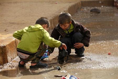 Children remove trash blocking the drains in the Al Inzarat district in Aleppo February 17, 2013. REUTERS/Hamid Khatib
