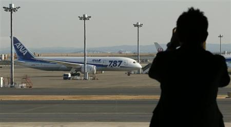 A man takes a photo of All Nippon Airways' (ANA) Boeing Co's 787 Dreamliner plane at Haneda airport in Tokyo January 29, 2013. REUTERS/Toru Hanai