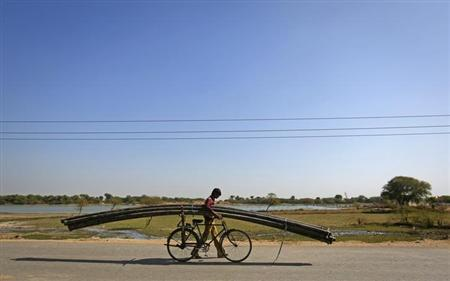 A farmer carries plastic pipes used for watering fields on his bicycle in Tonk, in Rajasthan January 20, 2013. REUTERS/Danish Siddiqui/Files