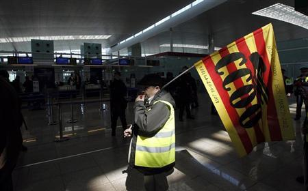A man holding a Comisiones Obreras (CCOO) trade union flag walks past Iberia's check-in desk during an Iberia workers strike at Terminal 1 of Barcelona's airport, March 8, 2013. REUTERS/Albert Gea