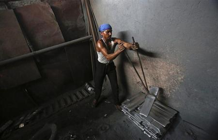 A labourer moves aluminium blocks at an aluminium smelting factory in Mumbai March 12, 2013. REUTERS/Vivek Prakash