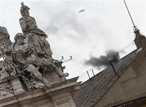 Black smoke rises from the chimney on the roof of the Sistine Chapel in the Vatican City, indicating that no decision has been made after the first voting session on the second day of voting for the election of a new pope, March 13, 2013. REUTERS/Alessandro Bianchi