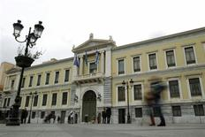 Commuters walk in front of the old headquarters of National Bank in Athens February 18, 2011. REUTERS/Yiorgos Karahalis