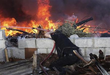 A man tries to extinguish a fire following shelling by forces loyal to Syria's President Bashar al-Assad, according to the Free Syrian Army, in Jobar area in Damascus March 13, 2013. REUTERS/ Mohammed Dimashkia