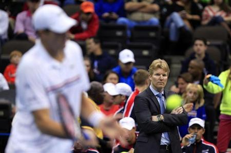 U.S. team captain Jim Courier (R) watches as John Isner practises before his match against Brazil's Thomaz Bellucci during the Davis Cup world group first round tennis tournament in Jacksonville, Florida February 3, 2013. REUTERS/Daron Dean