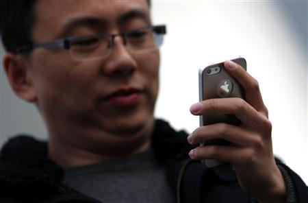 A man looks at the screen of his iPhone as he walks on a busy street in downtown Shanghai March 13, 2013. REUTERS/Carlos Barria