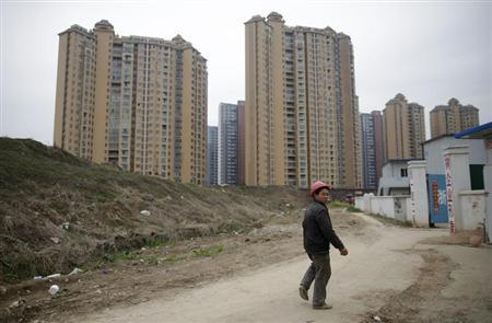 A worker looks back at a construction site next to a newly-built residential compound in Wuhan, Hubei province, March 11, 2013. REUTERS/Stringer