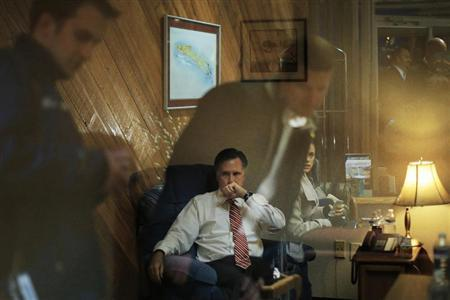 Staff members reflected off the window of the room where Republican presidential nominee Mitt Romney works before a campaign rally in North Canton, Ohio October 26, 2012. REUTERS/Brian Snyder
