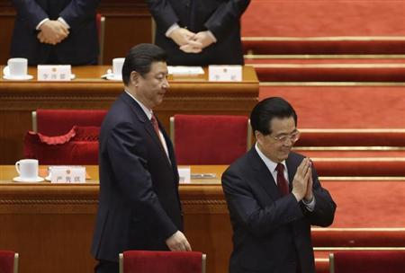 China's newly-elected President Xi Jinping walks past as China's former President Hu Jintao puts his palms together during the fourth plenary meeting of the National People's Congress (NPC) at the Great Hall of the People in Beijing, March 14, 2013. REUTERS/Jason Lee