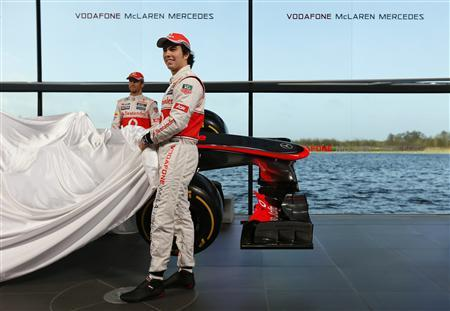 McLaren Formula One drivers Jenson Button of Britain (L) and Sergio Perez of Mexico unveil the McLaren MP4-28 car at the company's headquarters in Woking, southern England January 31, 2013. REUTERS/Stefan Wermuth