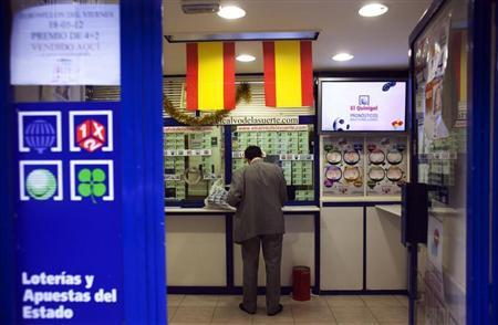A customer stands inside a lottery a kiosk in central Madrid June 13, 2012. REUTERS/Susana Vera