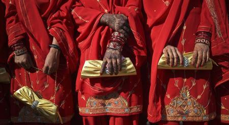 Brides-to-be, their hands decorated with henna, hold purses while standing side by side during a mass wedding ceremony in Karachi January 29, 2012. REUTERS/Akhtar Soomro/Files