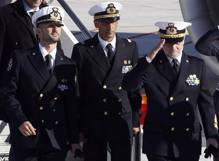 Italian marines Salvatore Girone (L) and Massimiliano Latorre (C) arrive with Italian Navy Chief of Staff Admiral Luigi Pinelli Mantelli at Ciampino airport in Rome, December 22, 2012. REUTERS/Alessandro Bianchi