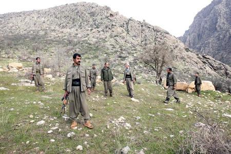 PKK fighters stand guard during the release of eight Turkish prisoners in the northern Iraqi city of Dohuk, March 13, 2013. Turkish Kurd militants freed a group of Turkish soldiers and officials they had held in the mountains of northern Iraq for more than a year on Wednesday, the first concrete step in efforts to end their 28-year-old insurgency. The six soldiers, a police officer and a local official looked in good health and wore clean clothes as they were handed to a delegation of Turkish rights activists and pro-Kurdish politicians on the remote Sargali plain. REUTERS/Azad Lashkari