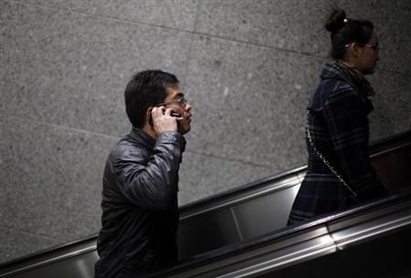 A man talks on his iPhone as he takes the escalator out of a subway station in downtown Shanghai March 13, 2013. REUTERS/Carlos Barria/Files