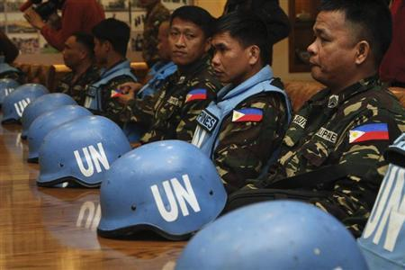 Filipino U.N. peacekeepers, part of a group of 21 peacekeepers held by rebels for three days in southern Syria, wait to address a news conference at the headquarters of the General Command of the Jordanian Army in Amman March 9, 2013. REUTERS/Muhammad Hamed