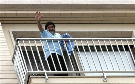 Former Argentine soccer star Diego Maradona waves as he appears on a balcony in Naples February 26, 2013. REUTERS/Ciro De Luca