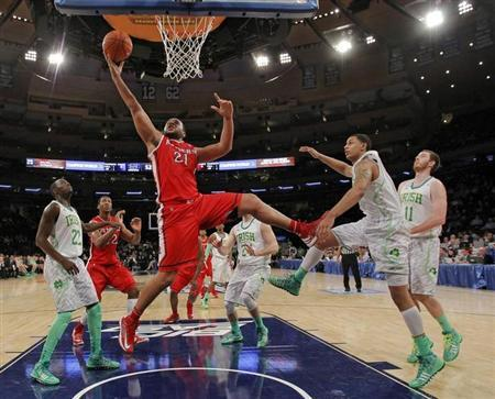 Rutgers Scarlet Knights forward Austin Johnson (21) drives for a layup through Notre Dame Fighting Irish guard Jerian Grant (22), forward Zach Auguste (RC) and center Garrick Sherman (11) during the second half of their NCAA men's championship basketball game at the 2013 Big East Tournament in New York, March 13, 2013. REUTERS/Ray Stubblebine