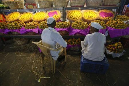 Fruit vendors sit in front of a display of mangoes at a wholesale market in Mumbai March 14, 2013. REUTERS/Vivek Prakash