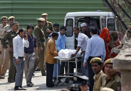 Hospital staff and relatives load the body of Ram Singh, the driver of the bus in which a young woman was gang-raped and fatally injured three months ago, into an ambulance after a post-mortem at a hospital in New Delhi March 12, 2013. REUTERS/Adnan Abidi