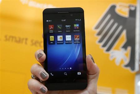 A woman holds a BlackBerry Z10 smartphone featuring high security Secusite software, used for governmental communication, at the booth of Secusmart during preparations at the CeBit computer fair in Hanover, March, 4, 2013. REUTERS/Fabrizio Bensch