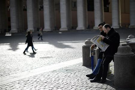 Men read an Italian newspaper showing the newly elected Pope Francis on its front page in Saint Peter's Square at the Vatican March 14, 2013. REUTERS/Dylan Martinez