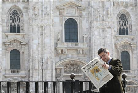 A man reads an Italian newspaper showing the newly elected Pope Francis on its front page in Duomo square in downtown Milan March 14, 2013. REUTERS/Alessandro Garofalo