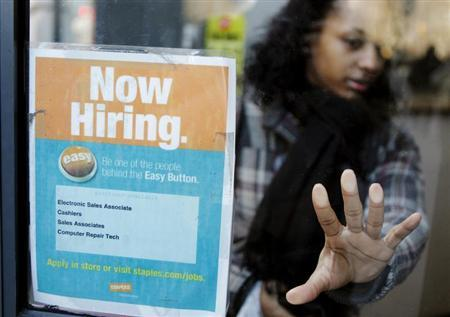 A woman opens a glass door with a ''Now Hiring'' sign on it as she enters a Staples store in New York March 3, 2011. REUTERS/Lucas Jackson