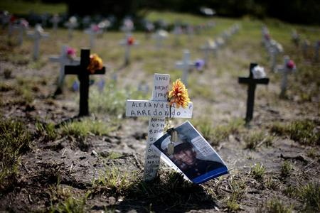 A photograph and 'dog tags' of 20-year-old U.S. Marine Alexander Arredondo, killed in Najaf, Iraq on August 25, 2004, lay attached to a cross at a symbolic cemetery at ''Camp Casey'' near the ranch of U.S. President George W. Bush in Crawford, Texas, in this April 6, 2007 file photo. REUTERS/Jason Reed/files