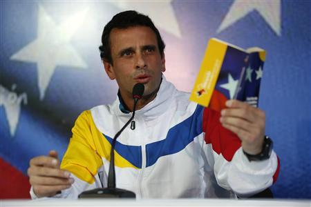 Venezuela's opposition leader and presidential candidate Henrique Capriles shows the Venezuelan constitution during a news conference in Caracas March 11, 2013. REUTERS/Tomas Bravo