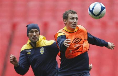 Daniel Majstorovic (L) and Alexander Gerndt of Sweden keep their eyes on the ball during a team training session ahead of their country's friendly soccer match against England tomorrow, in London November 14, 2011. REUTERS/Andrew Winning/Files