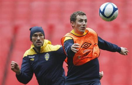 Daniel Majstorovic (L) and Alexander Gerndt of Sweden keep their eyes on the ball during a team training session in London November 14, 2011. REUTERS/Andrew Winning