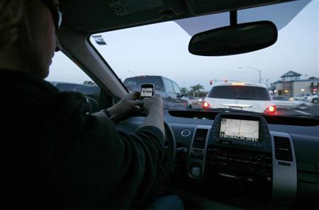 A driver uses his smart phone while in traffic in Encinitas, California December 10, 2009. REUTERS/Mike Blake