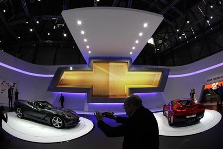 Visitors take pictures of Corvette cars on the Chevrolet booth during the second media day of the 83rd Geneva Car Show at the Palexpo Arena in Geneva March 6, 2013. REUTERS/Denis Balibouse