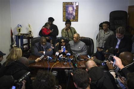 Carol Gray (centre L) shows a photograph of her late son Kimani Gray, who was killed in a New York Police Department shooting, next to City Councilman Charles Barron (centre R) and her lawyer Kenneth Montgomery (L) during a news conference in the Brooklyn borough of New York, March 14, 2013. REUTERS/Lucas Jackson