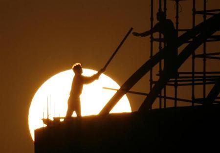 Labourers work at a construction site as sun sets in New Delhi February 16, 2008. REUTERS/Adnan Abidi/Files
