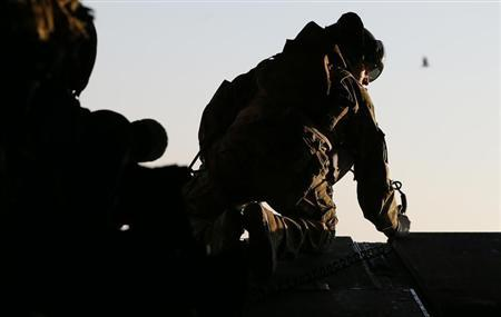 A British soldier looks out from the rear of a Chinook helicopter on the way to Forward Operating Base Price in Helmand Province, Afghanistan December 20, 2012. REUTERS/Stefan Wermuth