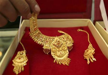 A shopkeeper displays gold jewellery for the camera at a jewellery shop in Jammu July 14, 2009. REUTERS/Mukesh Gupta/Files