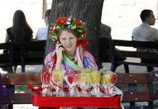 Одетая в национальный костюм уличная торговка сладостями говорит по телефону в центре Львова 22 июня 2011 года. Европейский союз вслед за США призвал Украину отказаться от идеи пересмотреть согласованные с ВТО импортные пошлины и предупредил, что это осложнит переговоры о зоне свободной торговли, которые Киев надеется завершить до конца года. REUTERS/Gleb Garanich